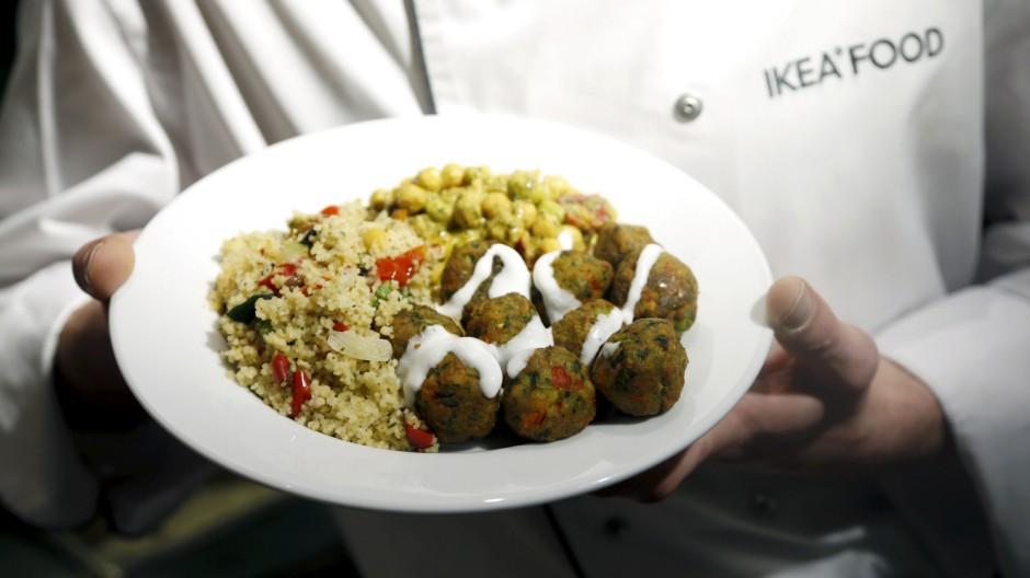 A cook displays a plate with the new 'Veggie balls' during its official launch at a IKEA store in Brussels