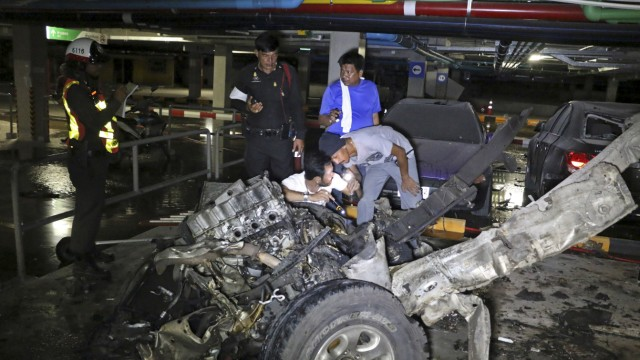 Police officers inspect the site of a car bomb blast at a car park of a shopping mall in Koh Samui