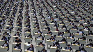 Students take an examination on an open-air playground at a high school in Yichuan