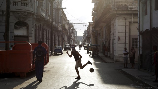 A young man plays soccer on a street in Havana