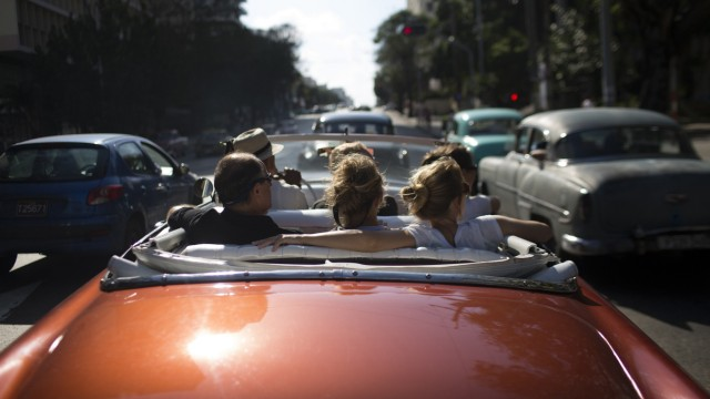 Tourists take a ride in a convertible car in Havana, January 6, 2014.