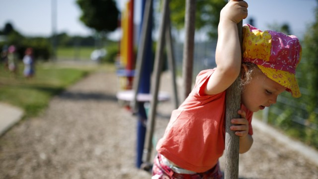 Three year-old Sarah balances on obstacle course in the outdoor area of a Kindergarten in Hanau