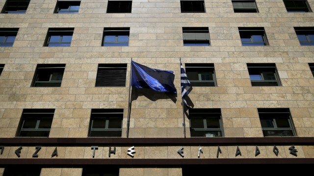 An EU flag flutters next to a Greek flag on the facade of the Bank of Greece headquarters in Athens