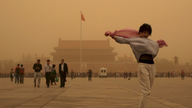 A tourist gestures as she poses for a photograph at Tiananmen Square during a sandstorm in Beijing