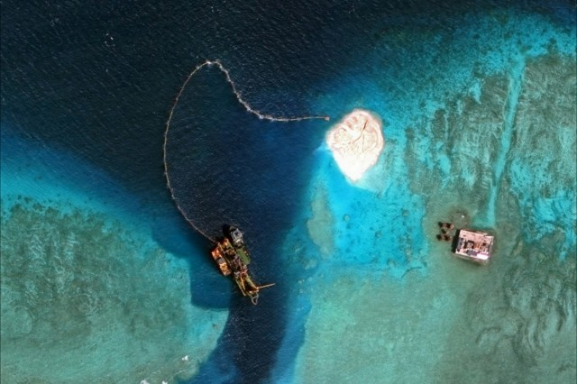 Satellite image shows dredger operating at the southern entrance to the Mischief Reef