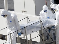 Italian coastguard personnel in protective clothing carry the body of a dead immigrant off their ship Bruno Gregoretti in Senglea