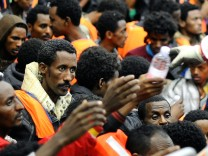 Migrants from Sub-Saharian areas receive bottles of water on a rescue boat of Italy's Navy ship San Giorgio after being rescued in open international waters in the Mediterranean Sea between the Italian and the Libyan coasts