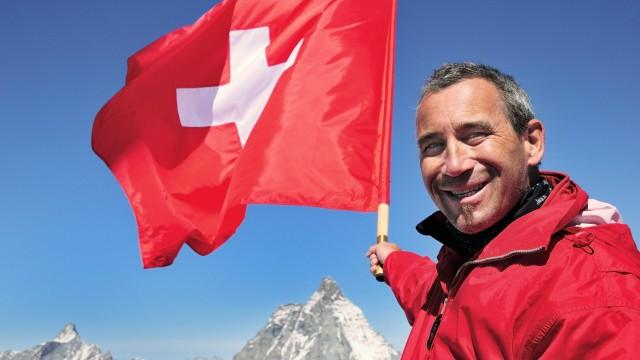 Tourist mit Schweizer Fahne über dem Matterhorn 4478 m Klein Matterhorn Zermatt Kanton Wallis S