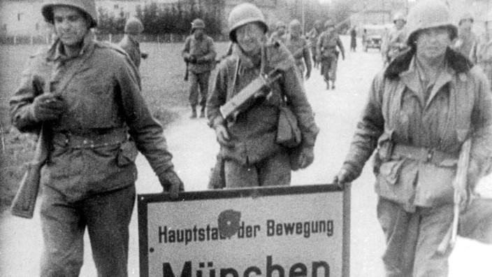 Amerikanische Soldaten mit einem Münchener Ortsschild, 1945