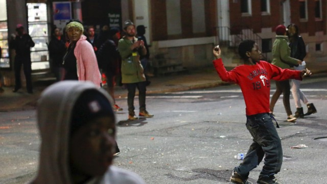 A child throws a rock at police as protesters gather for a rally to protest the death of Freddie Gray who died following an arrest in Baltimore, Maryland