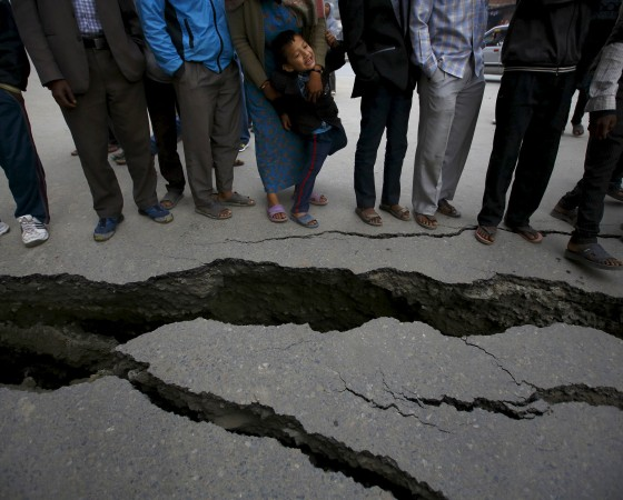 People gather near the cracks on the road caused by an earthquake in Bhaktapur