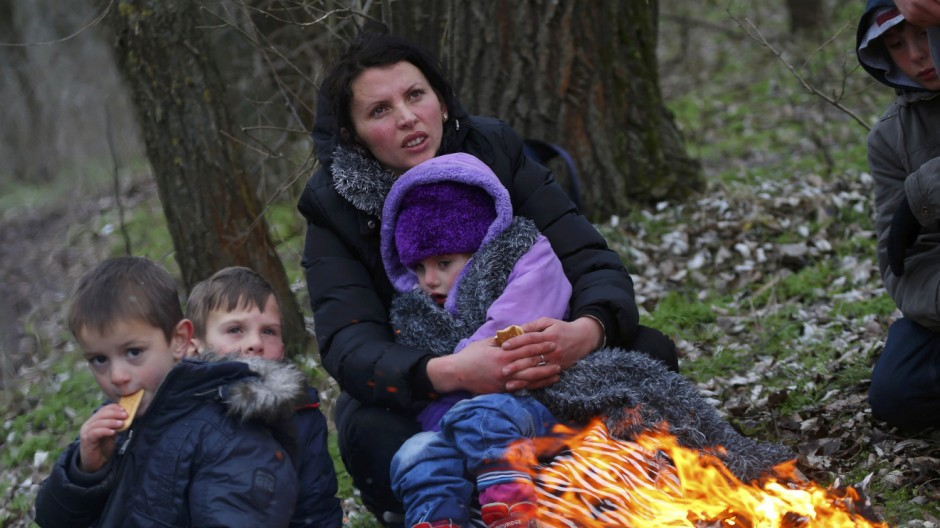 A Kosovar woman holds her child as they warm up around an open fire after they crossed illegally the Hungarian-Serbian border near the village of Asotthalom