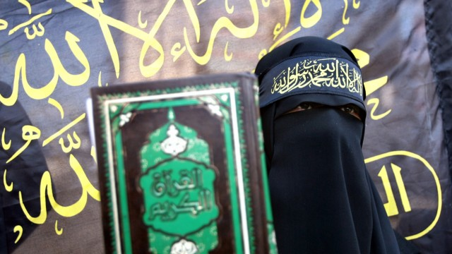 Palestinian woman from Islamic jihad holds Koran in front of Islamic Jihad flag during protest in Gaza City