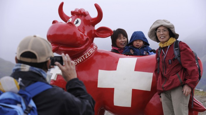 Japanese tourists pose for a photo with an artificial cow in Zermatt