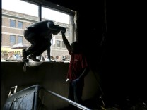 A man climbs through broken window as members of community clean up recently looted and burned CVS store leave because of concerns about building's stability in Baltimore, Maryland
