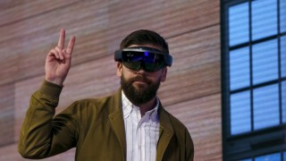 A man gestures while wearing a device featuring Windows Holographic technology at Microsoft Build in San Francisco