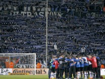 Arminia Bielefeld fans show their support as team gathers on the pitch after losing to VfL Wolfsburg in the German Cup in Bielefeld