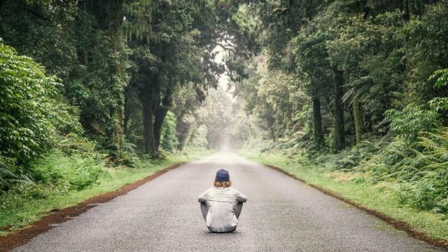 New Zealand South Island Jackson Bay Haast Jackson Bay Road young man sitting on road model rele