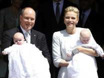 Prince Albert II of Monaco and his wife Princess Charlene hold their twins Prince Jacques and Princess Gabriella as they leave Monaco's Cathedral