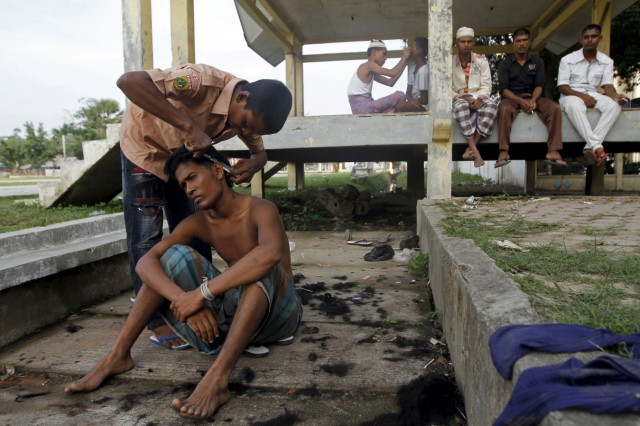 Migrants, believed to be Rohingya, cut each others' hair inside a shelter after being rescued from boats at Lhoksukon