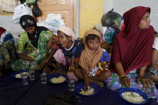 Migrants believed to be Rohingya take their breakfast inside a shelter after being rescued from boats at Lhoksukon