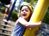 Two year-old Kaethe laughs as she balances on obstacle course in the outdoor area of a Kindergarten in Hanau
