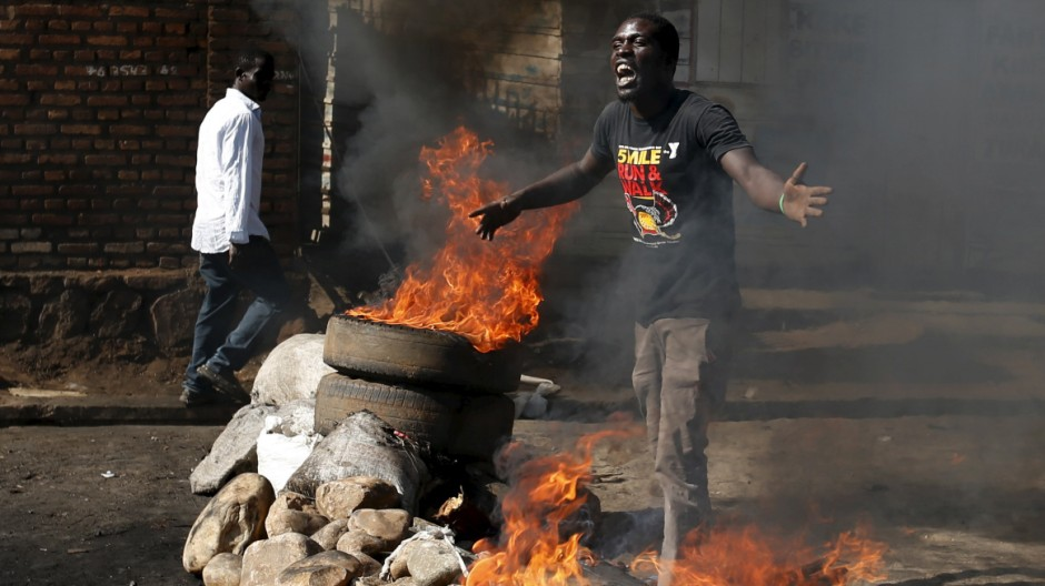 A protester gestures in front of a burning barricade in Bujumbura
