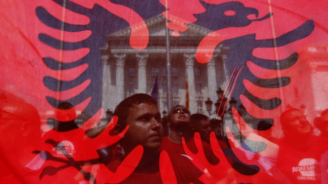 Anti-government protesters are seen through an Albanian flag as they demonstrate in front of Prime Minister Nikola Gruevski's government office in Skopje