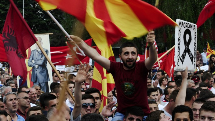 Protesters wave Macedonian and Albanian flags during an anti-government demonstration in Skopje