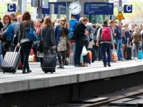 Passengers wait on a platform during a strike by GDL train drivers union at the main train station in Berlin