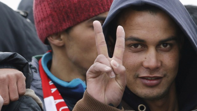 Moroccan citizen Touil Abdelmajid makes a victory sign as he arrives with migrants on the Italian navy ship Orione at Porto Empedocle harbour in Sicily