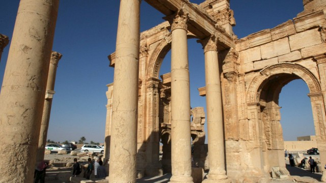 Tourists walk in the historical city of Palmyra