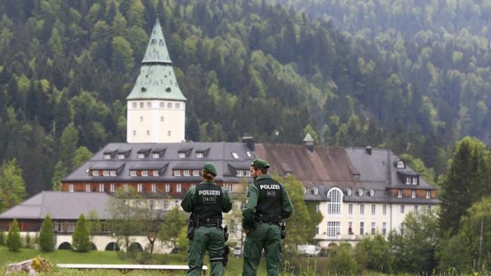 Members of the German riot police unit 'Bayerische Bereitschaftspolizei' observe the hotel castle Elmau in Kruen