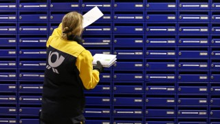File photo of Deutsche Post postwoman dropping a letter into a mailbox