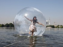 Woman tests Walk Wather Ball on the Alster lake in Hamburg