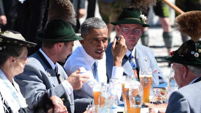 Obama beim G7-Gipfel sitzt mit Einheimischen am Tisch und trinkt Bier.
