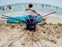 Ein Eimer mit Strohhalmen steht am Strand von Arenal auf Mallorca (Spanien).
