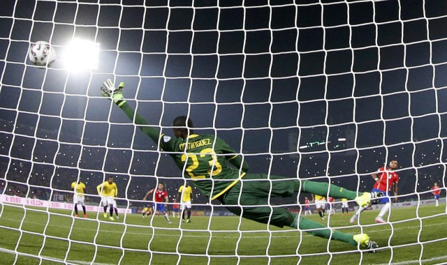 Chile's Vidal scores on a penalty kick against Ecuador's goalie Dominguez during the opening match of the Copa America 2015 soccer tournament in the National Stadium in Santiago