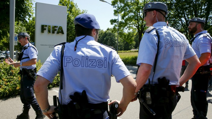 Swiss police officers stand in front of the entrance of the FIFA headquarters in Zurich