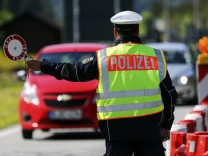 A policeman stops cars at the German-Austrian border near Mittenwald