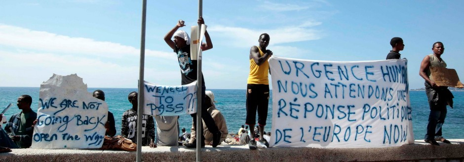 A group of migrants shout slogans and display a banner at the Saint Ludovic border crossing on the Mediterranean Sea between Vintimille, Italy and Menton