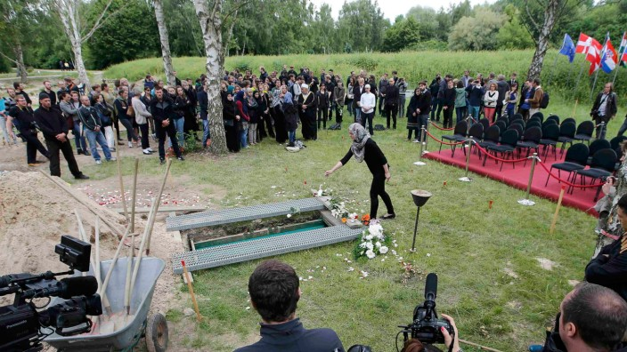 A woman pays her respects during a muslim funeral a female refugee at Gatow cemetery in Berlin