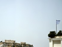 Ancient Parthenon temple is seen atop the Acropolis Hill archaeological site as a Greek national flag flutters from the roof of a building in central Athens