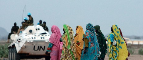 Displaced Sudanese women walk past an armoured personnel carrier (APC) of United Nations-African Union Mission in Nyala, southern Darfur