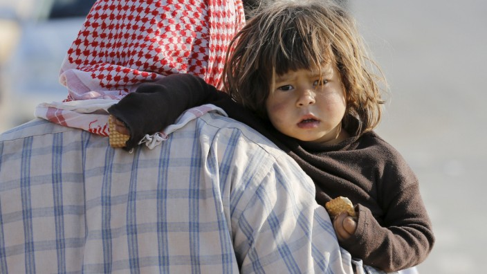A Syrian refugee man holds a child as he pauses at the Akcakale border gate after crossing into Turkey in Sanliurfa province, Turkey