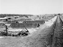 Erdhütten in einem KZ-Außenlager bei Kaufering. Aufnahme vom 29. April 1945 nach der Befreiung durch die US-Armee.