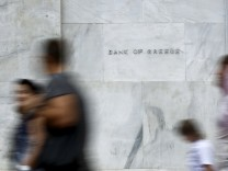 People walk past the Bank of Greece in Athens