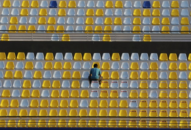 A man attaches stickers on the seats of the Estadio Sausalito stadium in Vina del Mar City, Chile