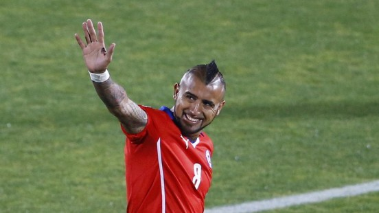 Chile's Arturo Vidal waves ahead of the first round Copa America 2015 soccer match against Bolivia at the National Stadium in Santiago