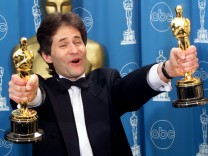 James Horner holds up two Oscars after winning for Best Original Song and Original Dramatic Score at Academy Awards in Los Angeles